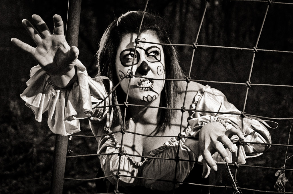 Ivonne as a zombie reaching through a fence